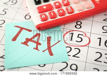 Paper sheet with text TAX and red calculator on calendar