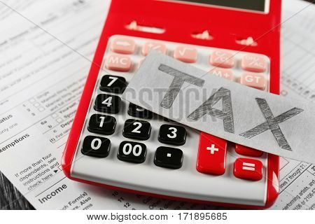 Paper sheet with text TAX on red calculator
