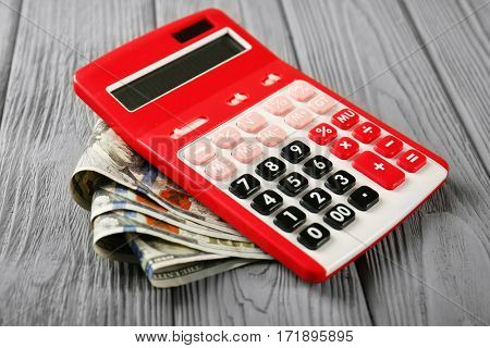 Calculator and money on wooden table