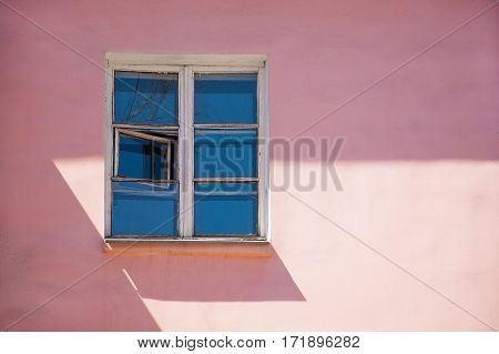 Pink wall of the building with white window
