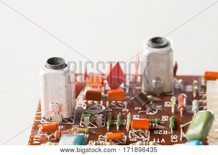 Old resistors capacitors close-up, selective focus. Vintage design circuit board and colorful electronic components. Shallow depth of field