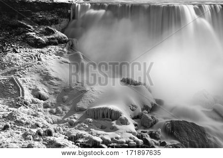 Snow and ice covered path leading up the steep side of a rocky waterfall winter scene northern extreme adventure travel scene