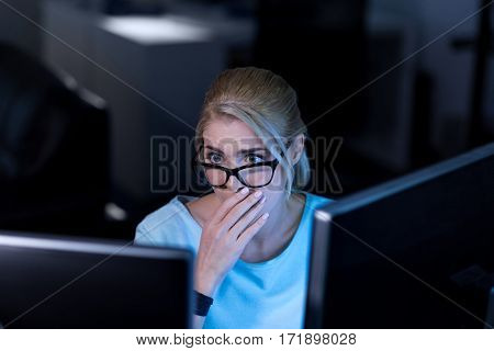 Shocking information. Young surprised shocked programmer sitting in the office and using computers while working and expressing emotions