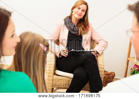 A family is talking to a psycho therapist