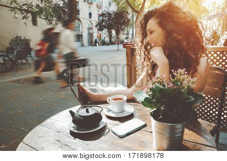 Young curly woman talking in video chat with her friend via digital tablet while sitting in street cafe with cup of good black tea smiling girl watching comedy movie on her touch pad during breakfast
