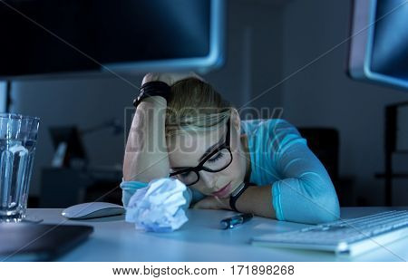 Difficult working hours. Upset exhausted tired techie sitting in the office while feeling tired and falling asleep