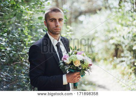Beautiful wedding bouquet in hands of the groom.