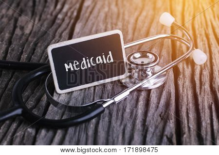 Stethoscope On Wood With Medicaid Word As Medical Concept.