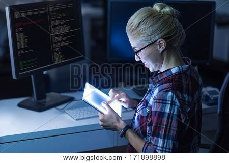 Revealing bug in the program. Delighted involved proficient hacker sitting in the dark lighted room and using modern gadgets while expressing concentration and finding the error