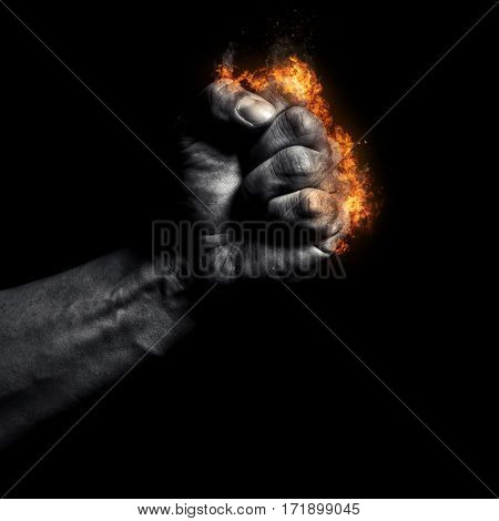 Burning man's clenched fist on a black background