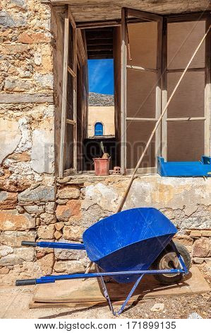 Blue wheelbarrow with blue box, blue sky and blue door and wall made from old stones.