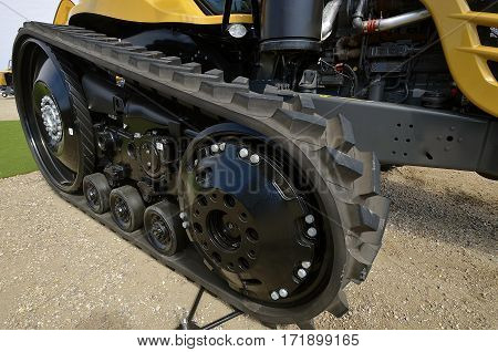 Narrow track with deep tread of a new gold colored tractor
