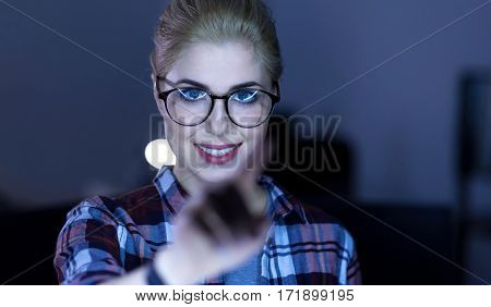 One touch technology. Positive smiling delighted IT girl standing in the dark lighted room and using modern gadget while expressing positivity and touching the invisible screen