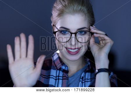 Technologies of our future. Positive smiling young IT girl standing in the dark lighted room and touching her glasses while expressing positivity and touching the invisible screen