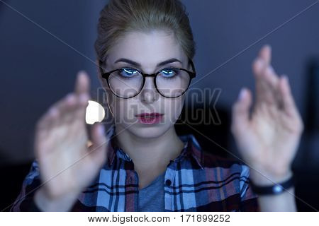 The invisible possibilities . Attentive involved young IT girl standing in the dark lighted room while expressing concentration and touching the invisible screen