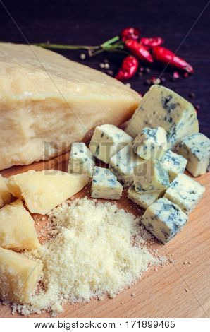 Grated Parmesan and sliced Blue cheese with chili pepper on wooden chopping board on dark background. Tasty appetizers. Selective focus.