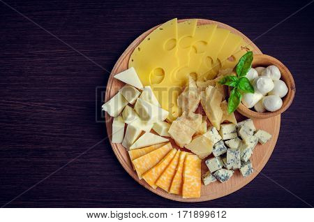 Cheese plate: Parmesan cheddar gouda mozzarella and other with basil on wooden board on dark background with place for text. Tasty appetizers. Top view. Copy space.