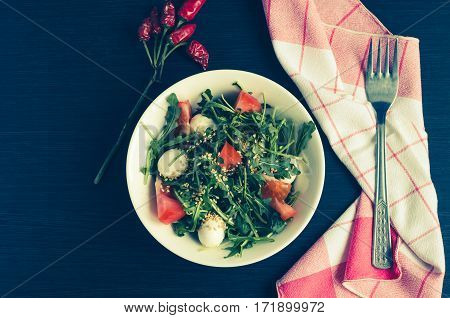Fresh summer salad with tomatoes fresh arugula leaves and mini mozzarella cheese on white plate over dark wooden baclground with place for text. Healthy diet food concept. Top view. Copy space.