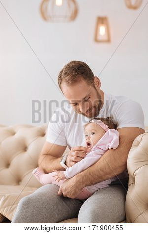 Look at these cheeks. Amused glad bearded father sitting on the settee at home and holding his baby while expressing positivity and care