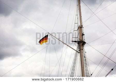 german flag on a sailing ship in front of an overcast sky