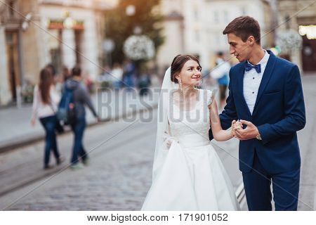 Wedding portrait of a happy couple. Stand and kissing on the streets of the old city.