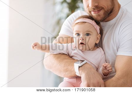 Interesting world around me. Surprised amazed involved baby girl lying in hands of the father and looking away while expressing interest