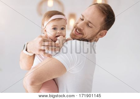 Pure happiness. Cute amiable little baby girl lying in hands of the young father and looking away while expressing positivity