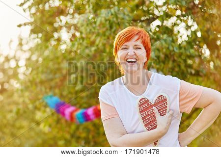Happy senior woman laughing and holding a heart at a summer party