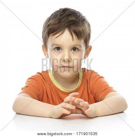 Portrait of a cute little boy sitting at table and fixing his eyes on you, isolated over white