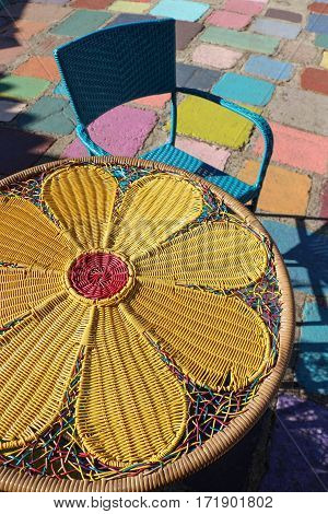 Colorful bistro table with woven yellow flower design and blue basket-weave chair in Balboa Park, San Diego
