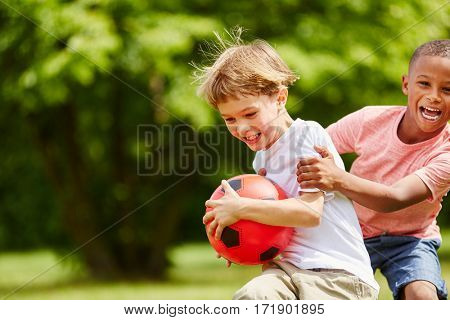 Two children having fun in summer playing with soccer ball as friends
