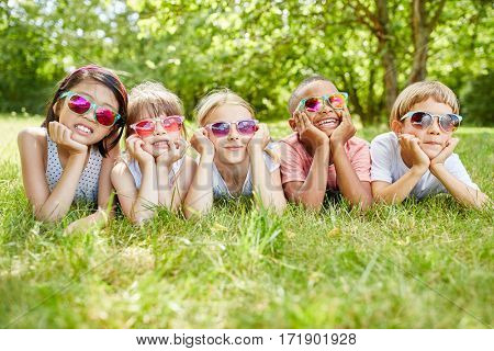 Interracial group of kids relaxing in summer vacation at the park