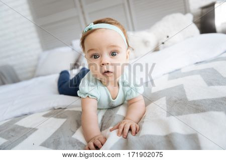 Exploring my room. Cute positive little girl lying on the bed in the bedroom and looking on the audience while expressing interest