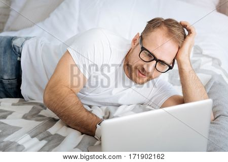 Working hours at home. Peaceful smiling cheerful man lying on the bed and using the laptop while expressing interest and surfing the Internet