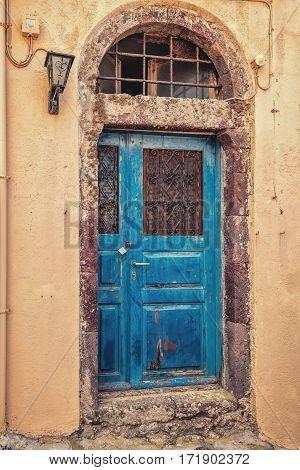 Blue door on old rusty wallat Santorini.
