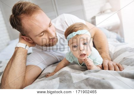 Full of different emotions. Delighted amazed charming toddler girl lying on the bed with her father and relaxing while expressing interest
