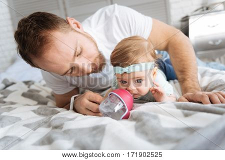 Time for eating. Careful young helpful father sitting in the bedroom and feeding his little daughter while holding the nipple bottle