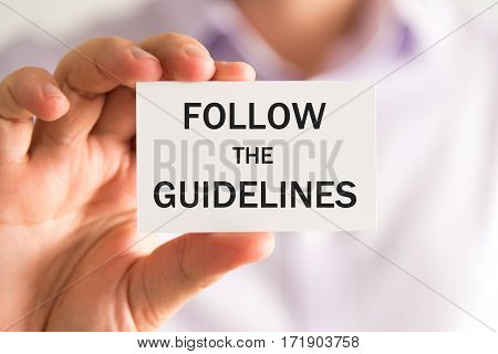 Businessman Holding Follow The Guidelines Card