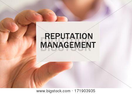 Businessman Holding Reputation Management Text Card
