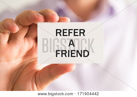 Businessman Holding Refer A Friend Text Card