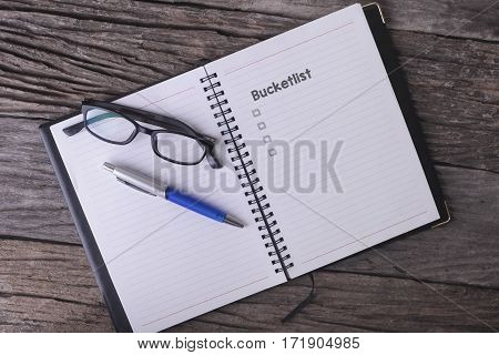 Conceptual,notebook On A Wooden Table. Open Diary, Glasses And Pen With Bucketlist Word.