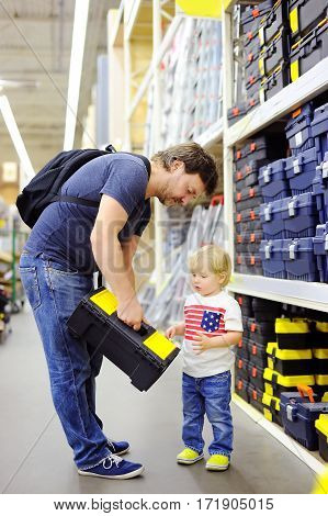 Father And His Son Choosing The Right Tool Box In A In A Hardware Store