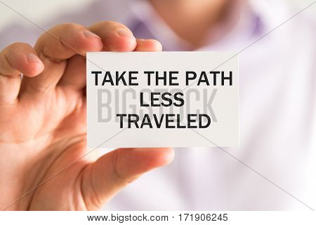 Businessman With Take The Path Less Traveled Card