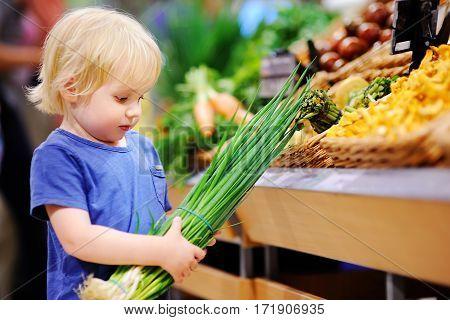 Cute Toddler Boy In A Food Store Choosing Fresh Organic Green Onion