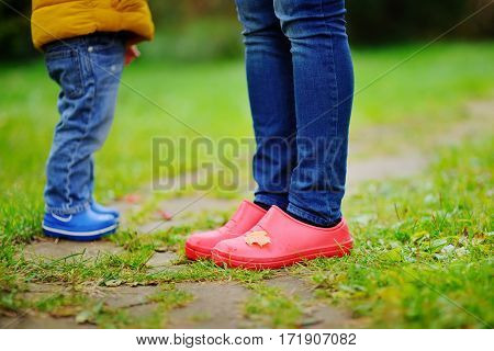 Close Up Photo Of Child And Adult Legs In Rubber Boots