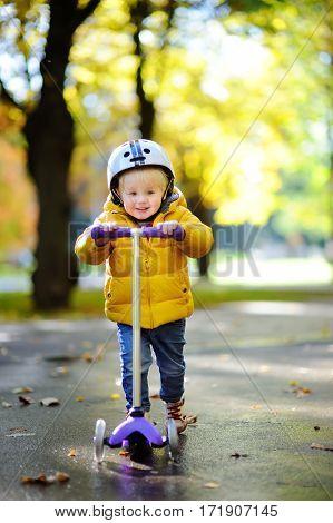 Toddler Boy In Helmet To Ride Scooter