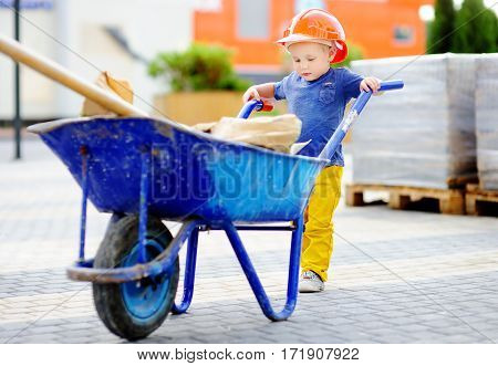 Portrait of cute toddler builder in hardhats with wheelbarrow working outdoors. Little boy`s dream concept