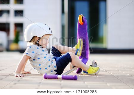 Toddler Boy Learning To Ride Scooter