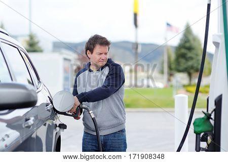 Man Filling Gasoline Fuel In Car