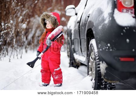 Cute Little Child Helping To Brush A Snow From A Car